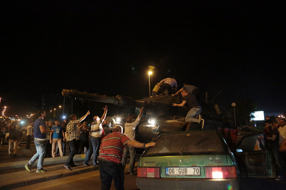 """Tanks move into position as Turkish people attempt to stop them, in Ankara, Turkey, late Friday, July 15, 2016. Turkey's armed forces said it """"fully seized control"""" of the country Friday and its president responded by calling on Turks to take to the streets in a show of support for the government. A loud explosion was heard in the capital, Ankara, fighter jets buzzed overhead, gunfire erupted outside military headquarters and vehicles blocked two major bridges in Istanbul. (AP Photo/Burhan Ozbilici)"""